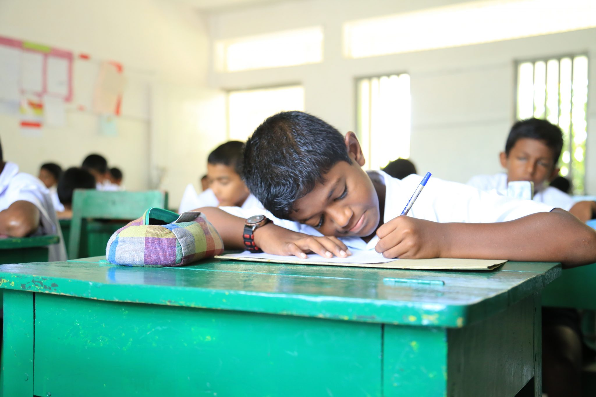 Middle school boy writing in class at Trinity College Kandy